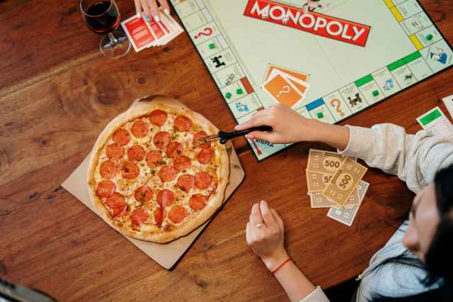 person holding pizza on brown wooden table