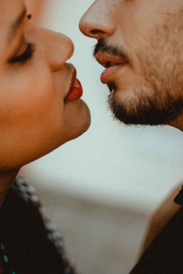crop ethnic woman with unrecognizable bearded beloved before kissing