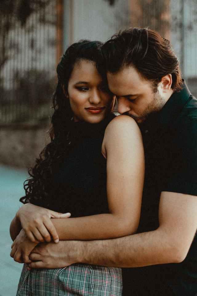 ethnic man embracing and kissing shoulder of dreamy beloved